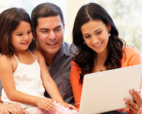 Hispanic-family-with-laptop-at-home